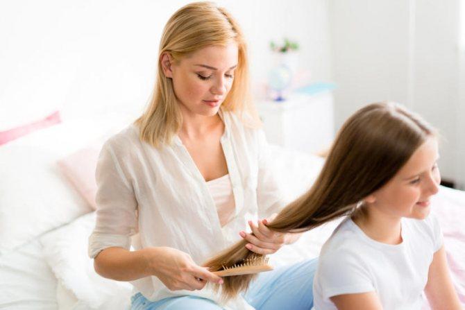 мама расчесывает дочке волосы